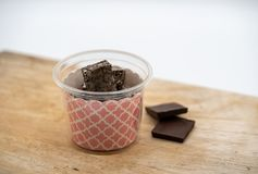 Homemade chocolate marshmallow treat bar in plastic cup with pin. K pattern on wooden board on white background royalty free stock images
