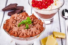 Homemade chocolate mousse in portion glasses on wooden background. Close up stock photo