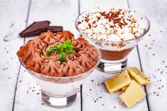 Homemade chocolate mousse in portion glasses on wooden background. Close up stock photography