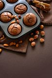 Homemade chocolate muffins brownies with cinnamon, almonds and hazelnuts on brown paper background Royalty Free Stock Photo