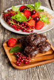 Homemade chocolate muffins with fresh strawberries and currants Royalty Free Stock Photo
