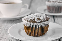 Homemade chocolate muffins with powdered sugar and coffee Stock Photos