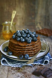 Homemade chocolate pancakes with fresh blueberry and honey. stock photography