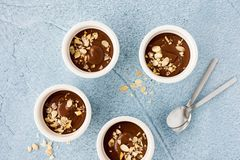 Homemade chocolate pudding in three white ceramic ramekins with roasted almond slivers and teaspoons on light blue concrete. Background. Top view royalty free stock photo