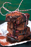 Homemade chocolate sweet brownies cakes with cherry and chocolate sauce or syrup on a dark background, horizontal Royalty Free Stock Images