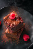 Homemade chocolate sweet brownies cakes with cherry and raspberries on a dark background Stock Photos