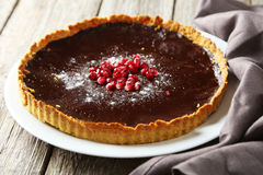 Homemade chocolate tart with pomegranate on a grey wooden background Stock Photo