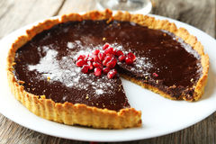 Homemade chocolate tart with pomegranate on a grey wooden background Stock Images