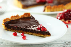 Homemade chocolate tart with pomegranate on a white wooden background Royalty Free Stock Photography