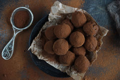 Homemade chocolate truffle candies with cocoa powder on craft paper, sweet dessert Stock Photos
