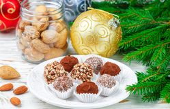 Homemade chocolate truffles with almonds, coconut and biscuits crumb. In a white plate on the table with fir branches and festive toys balls. Gift for Christmas stock images