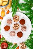 Homemade chocolate truffles with almonds, coconut and biscuits crumb in a white plate. On the table with fir branches and festive toys balls. Gift for Christmas royalty free stock images