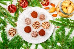 Homemade chocolate truffles with almonds, coconut and biscuits crumb in a white plate. On the table with fir branches and festive toys balls. Gift for Christmas stock photos