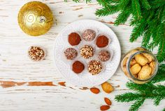 Homemade chocolate truffles with almonds, coconut and biscuits crumb. In a white plate on the table with fir branches and festive toys balls. Gift for Christmas royalty free stock images
