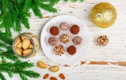 Homemade chocolate truffles with almonds, coconut and biscuits crumb. In a white plate on the table with fir branches and festive toys balls. Gift for Christmas stock photography