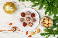 Homemade chocolate truffles with almonds, coconut and biscuits crumb. In a white plate on the table with fir branches and festive toys balls. Gift for Christmas royalty free stock image