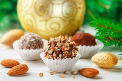 Homemade chocolate truffles with almonds, coconut and biscuits crumb. In a white plate on the table with fir branches and festive toys balls. Gift for Christmas royalty free stock photography