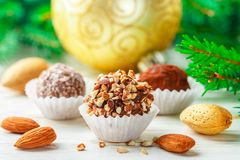 Homemade chocolate truffles with almonds, coconut and biscuits crumb. In a white plate on the table with fir branches and festive toys balls. Gift for Christmas stock photo