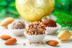 Homemade chocolate truffles with almonds, coconut and biscuits crumb. In a white plate on the table with fir branches and festive toys balls. Gift for Christmas stock photos
