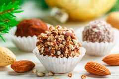 Homemade chocolate truffles with almonds, coconut and biscuits crumb. In a white plate on the table with fir branches and festive toys balls. Gift for Christmas stock image