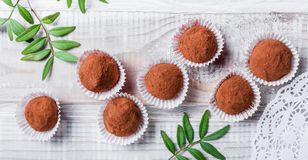Homemade Chocolate truffles candy dessert on wooden background close up. Delicious chocolate praline with decor. Top view stock photo