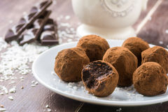 Homemade chocolate truffles with coconut flakes. Silky smooth homemade chocolate truffles with coconut flakes on a white round plate. Chocolate bars and vintage royalty free stock images