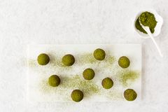 Homemade Chocolate Truffles dusted with Matcha Powder. Homemade chocolate truffles on a white marble chopping board dusted with green matcha tea powder.  Top Royalty Free Stock Photography