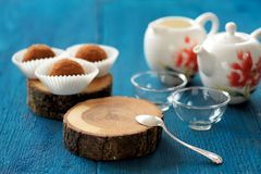 Homemade chocolate truffles, empty cups and teapots on navy blue Stock Photography