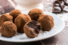Homemade chocolate truffles. Homemade healthy vegan chocolate truffles with dates, coconut flakes and rolled oats served on white plate stock photo