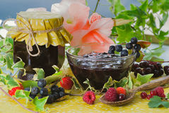 Homemade chokeberry confiture. Fresh homemade chokeberry confiture in glass served with different berries stock image