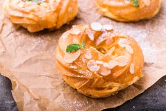Homemade choux pastry cake Paris Brest. With almond flakes and sugar powder. Decorated with small mint leaves. On parchment paper. Baking concept Royalty Free Stock Photos