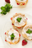 Homemade choux pastry rings with cottage cheese cream and strawberries decorated mint leaves Stock Photos
