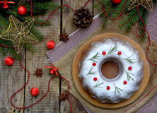 Homemade christmas cake with cranberry and new year tree decorations frame on wooden table background. Rustic style. Stock Images