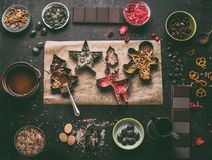 Homemade Christmas chocolate bars making. Christmas cutters with various toppings and flavorings. Melted chocolate in bowl stock photos
