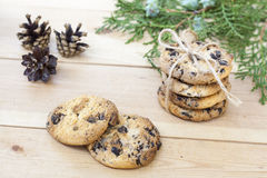 Homemade Christmas cookies with chocolate, nuts, cones, cinnamon and green arborvitae branch on a wooden table Royalty Free Stock Photo