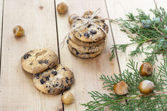 Homemade Christmas cookies with chocolate, nuts, cones, cinnamon and green arborvitae branch on a wooden table Stock Image
