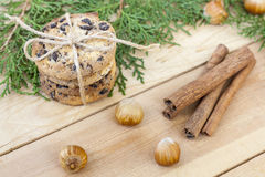 Homemade Christmas cookies with chocolate, nuts, cones, cinnamon and green arborvitae branch on a wooden table Royalty Free Stock Photography
