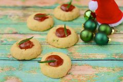 Homemade Christmas cookies. Homemade Christmas thumbprint rosemary cookies on green background Royalty Free Stock Images