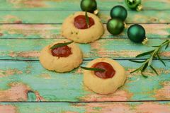 Homemade Christmas cookies. Homemade Christmas thumbprint rosemary cookies on green background Stock Photo