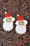 Homemade Christmas cookies. Two homemade Christmas cookies in the form of Santa Klaus with white beards and pointed red hats with pom poms on a background of royalty free stock image