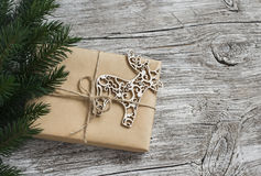 Homemade Christmas gift in kraft paper, wooden Christmas deer ornament, Christmas tree branches on rustic light wooden surface. Fr Stock Photography
