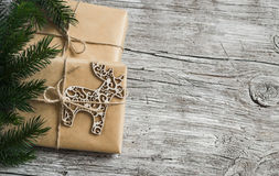 Homemade Christmas gift in kraft paper, wooden Christmas deer ornament, Christmas tree branches on rustic light wooden surface. Fr Royalty Free Stock Photos