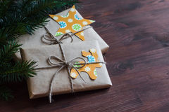 Homemade Christmas gifts in kraft paper with handmade tags and a Christmas tree on dark brown wooden surface. Stock Image