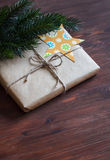 Homemade Christmas gifts in kraft paper with handmade tags and a Christmas tree on dark brown wooden surface. Royalty Free Stock Images