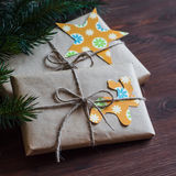 Homemade Christmas gifts in kraft paper with handmade tags and a Christmas tree on dark brown wooden surface. Royalty Free Stock Photos