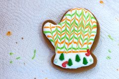 Homemade Christmas gingerbread decorated in the form of mittens on the background of a white napkin with the remains of glaze. royalty free stock images