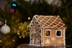 Homemade Christmas Gingerbread House. Beautiful tree lights and balls in the background. Homemade Christmas Gingerbread House displayed on a table. Christmas Stock Image