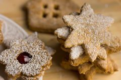 Homemade Christmas gingerbread and linzer cookies with jam powdered, on a wood board, close up Stock Photos