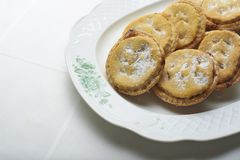 Homemade Christmas Mince pies on a white classic plate. Homemade Christmas Mince pies on a white classic plate over a table with a white tablecloth Royalty Free Stock Images