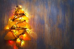 Homemade Christmas tree with lights illuminated on a wooden back. Ground, cardboard decoration royalty free stock photo